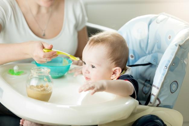 Porträt eines süßen, entzückend kleinen jungen, der im stuhl sitzt und vom löffel isst