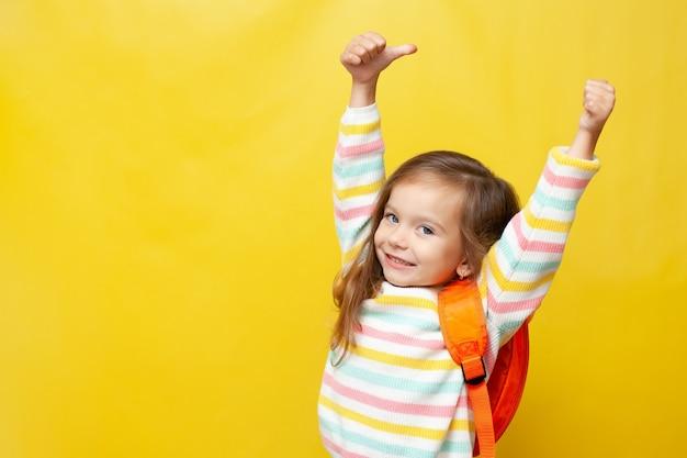Porträt eines süßen, fröhlich lachenden mädchens mit einem rucksack zurück zur schule daumen hoch