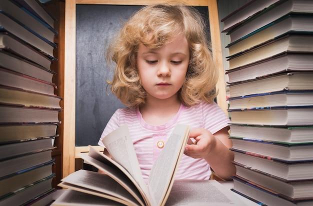 Porträt eines süßen, intelligenten mädchens, das ein buch liest, während es mit einem stapel bücher am tisch sitzt