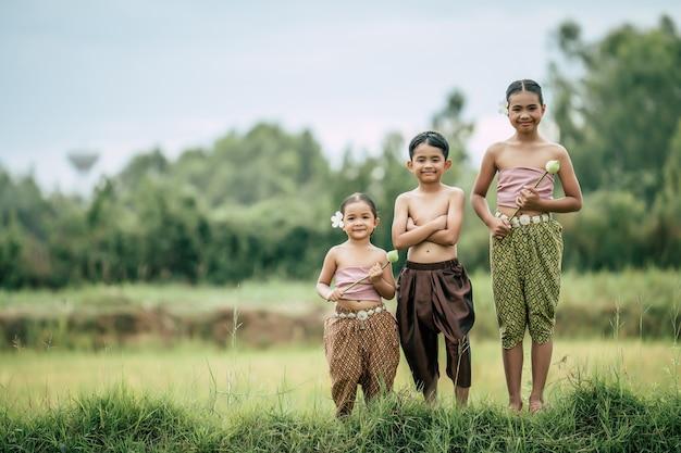 Porträt eines süßen jungen mit gekreuzten armen und zwei hübschen mädchen in traditioneller thailändischer kleidung setzen schöne blume auf ihr ohr, die im reisfeld steht, lächeln, platz kopieren