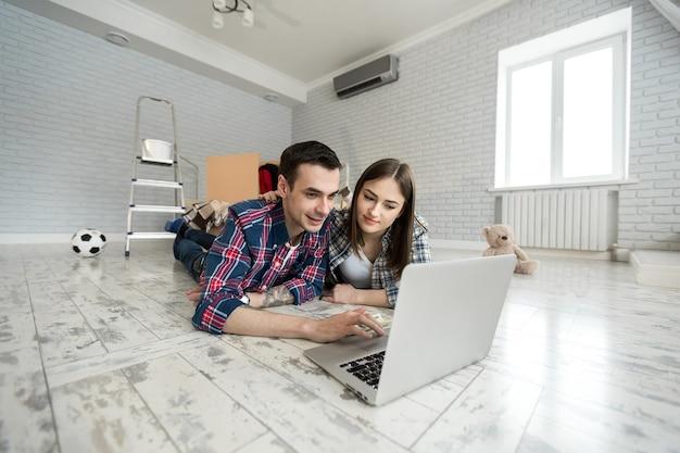 Porträt eines süßen jungen paares, das zu hause auf dem boden liegt und das budget mit dem laptop verwaltet