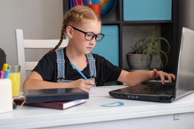 Porträt eines süßen kaukasischen rotschopfmädchens in brillen mit laptop beim lernen zu hause, fernbildungskonzept. hausaufgaben schreiben. quarantäne. zurück zum schulkonzept.