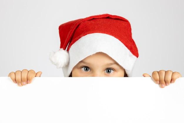 Porträt eines süßen kindes in rotem weihnachtsmann-hut versteckt gesicht hinter weißem leerem banner isoliert auf...
