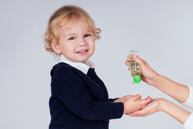 Porträt eines süßen kleinen blonden jungen, der antibakterielles antiseptisches gel auf die hände aufträgt, antibakterielle viren im studio auf weißem hintergrund. baby-epidemie-schutz, nahaufnahme der mutterhand