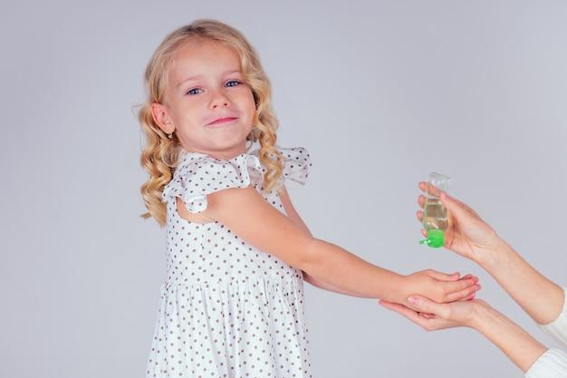 Porträt eines süßen kleinen blonden mädchens, das antibakterielles antiseptisches gel auf die hände aufträgt, antibakterielle viren im studio auf weißem hintergrund. baby-epidemie-schutz, nahaufnahme der mutterhand