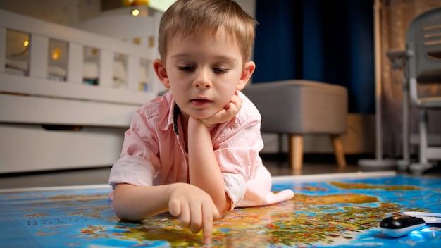 Porträt eines süßen kleinen jungen, der mit den fingern über die große weltkarte geht. konzept von reisen, tourismus und kindererziehung. erkundungen und entdeckungen für kinder.
