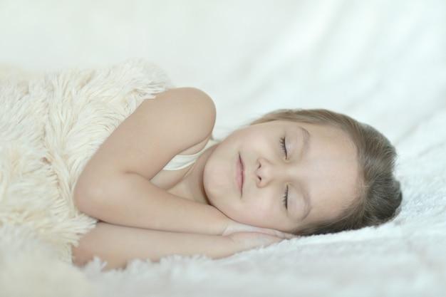 Porträt eines süßen kleinen mädchens, das im bett schläft