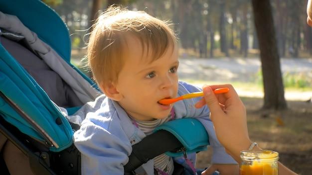 Porträt eines süßen kleinkindjungen, der brei vom löffel isst, während er im kinderwagen im park sitzt.