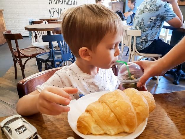 Porträt eines süßen kleinkindjungen, der im café kalten tee aus stroh trinkt