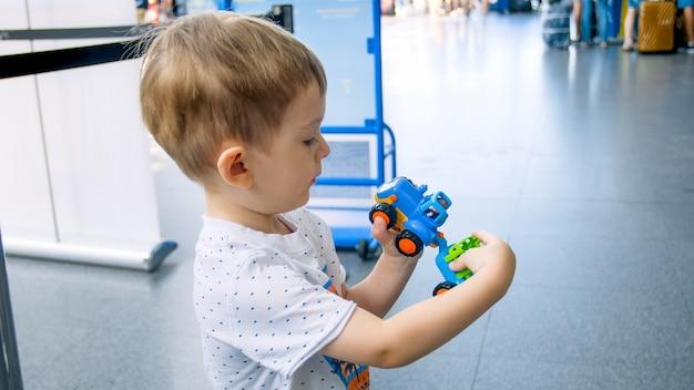 Porträt eines süßen kleinkindjungen, der mit spielzeugauto im modernen flughafenterminal spielt, während er auf den flug wartet.