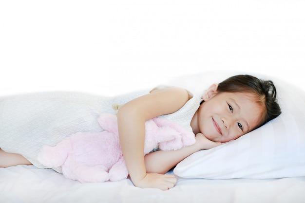 Porträt eines süßen lächelnden kleinen asiatischen mädchens, das morgens auf bett mit dem betrachten der kamera liegt.