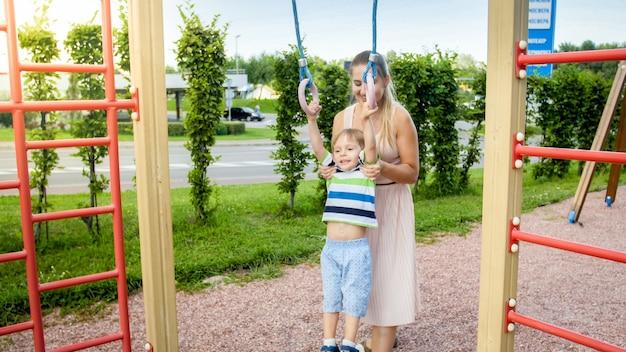 Porträt eines süßen, lächelnden kleinkindjungen, der mit seiner mutter auf dem kinderspielplatz an den ringen hängt