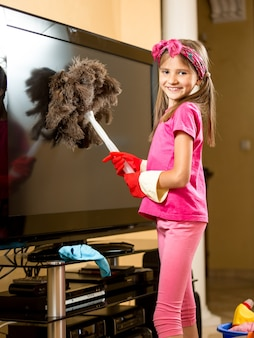 Porträt eines süßen lächelnden mädchens, das den fernseher im wohnzimmer vom staub säubert