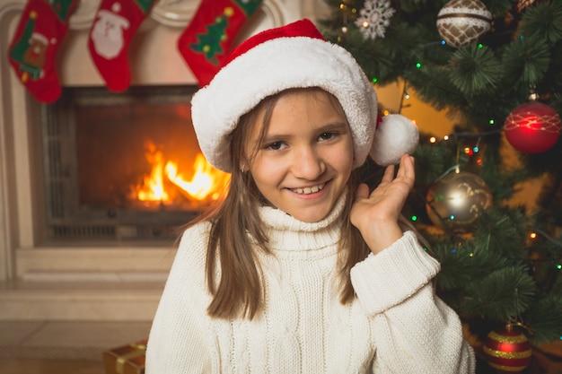 Porträt eines süßen mädchens in weißem pullover und weihnachtsmütze, das am brennenden kamin im wohnzimmer posiert