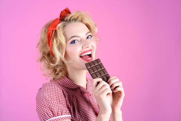 Porträt eines süßen pinup-mädchens mit schokolade auf rosa hintergrund, nahaufnahme von pin-up-stil lächelnd