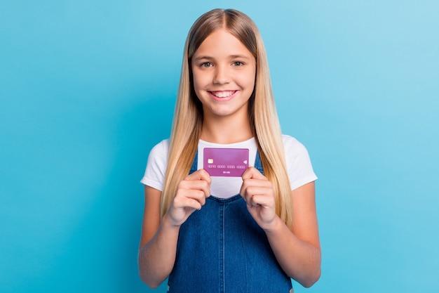 Porträt eines süßen, schönen blonden mädchens mit langen haaren, das ein lässiges outfit mit kreditkarte zeigt, das auf pastellblauem hintergrund isoliert ist