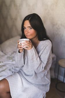 Porträt eines tagesträumenmädchens, das kaffeetasse hält