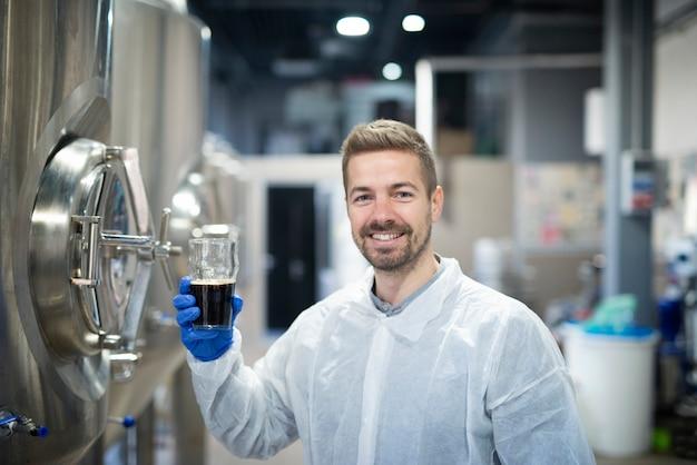 Porträt eines technologen, der die produktqualität in einer produktionsanlage für getränkealkohol testet