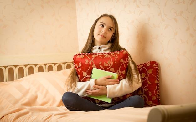 Porträt eines teenager-mädchens, das mit ihrem privaten tagebuch auf dem bett sitzt