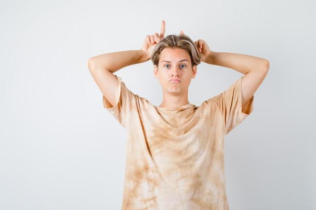 Porträt eines teenagerjungen, der die finger als stierhörner im t-shirt über dem kopf hält und schmollende vorderansicht sieht