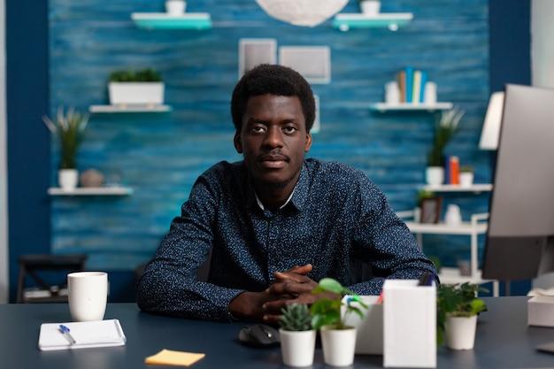 Porträt eines teenagers, der am schreibtisch im wohnzimmer sitzt