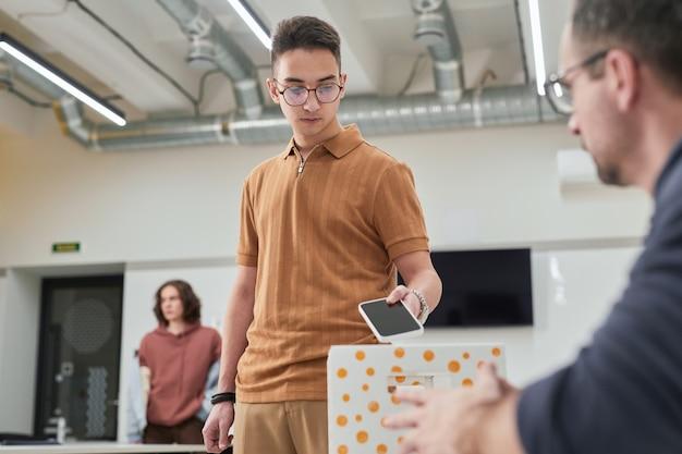 Porträt eines teenagers, der in der schule smartphone in box in kein gadget-klassenzimmer steckt, kopierraum