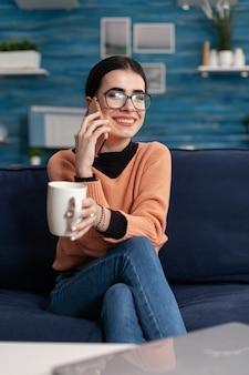 Porträt eines teenagers, der über den lebensstil auf einem modernen smartphone spricht, während er mit ihrer freundin lacht, die auf der couch im wohnzimmer sitzt. junge frau, die spaß während des lustigen lebensstil-gesprächsanrufs hat