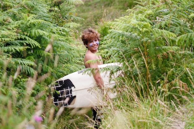 Porträt eines teenagers in der natur mit einem surfbrett unter dem arm