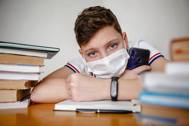 Porträt eines teenagers zu hause in einer maske hinter lehrbüchern