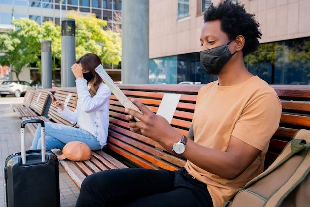 Porträt eines touristenvolkes, das außerhalb des flughafens oder des bahnhofs wartet, während auf bank sitzt und abstand hält