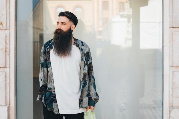 Porträt eines tragenden hemdes des stilvollen mannes, das vor glas steht