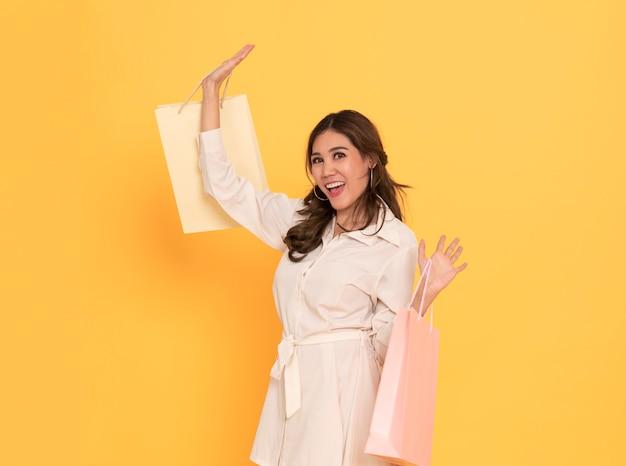 Porträt eines tragenden kleides des aufgeregten schönen asiatischen mädchens, das einkaufstaschen hält