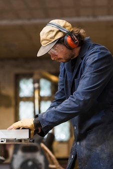 Porträt eines tragenden ohrschützers des männlichen tischlers, der in der werkstatt arbeitet