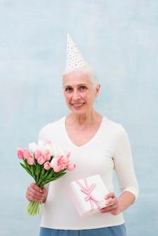Porträt eines tragenden partyhutes der älteren frau, der blumenblumenstrauß und geschenkbox hält