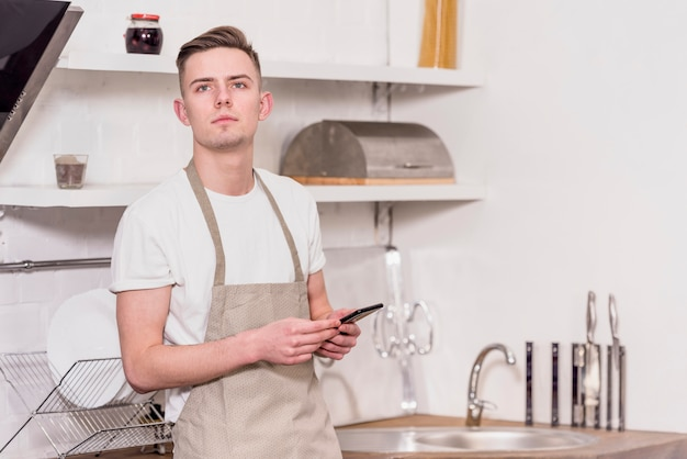 Porträt eines tragenden schutzblechs des jungen mannes, das in der hand den handy weg schaut hält