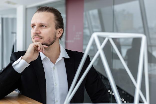 Porträt eines traumhaft ernsten mannes, der kinn auf seine hand legte, die im modernen interieur sitzt