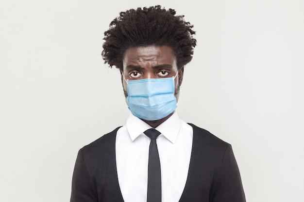 Porträt eines traurigen allein jungen arbeitermannes, der schwarzen anzug mit chirurgischer medizinischer maske trägt und die kamera mit müdem, alleinigem oder verärgertem gesicht ansieht. indoor-studioaufnahme auf grauem hintergrund isoliert.