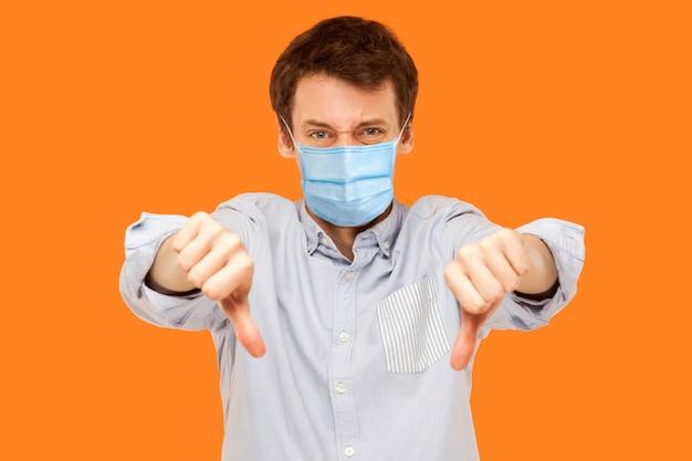Porträt eines traurigen jungen arbeitermannes mit chirurgischer medizinischer maske, der mit den daumen nach unten steht und die kamera mit unzufriedenem gesicht betrachtet. indoor-studioaufnahme auf orangem hintergrund isoliert.