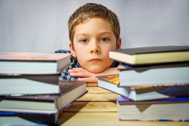Porträt eines traurigen jungen, der zwischen kinderbüchern liegt und auf einem holztisch steht.