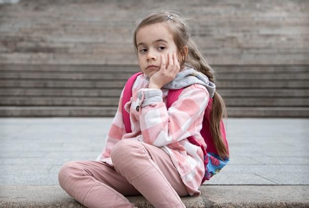 Porträt eines traurigen kleinen mädchens mit einem rucksack, das auf der treppe sitzt. zurück zur schule.