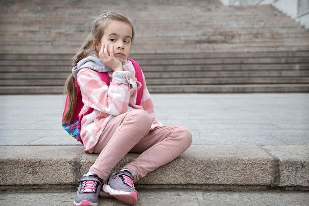Porträt eines traurigen kleinen mädchens mit einer aktentasche auf dem rücken, das auf der treppe sitzt. zurück zur schule.
