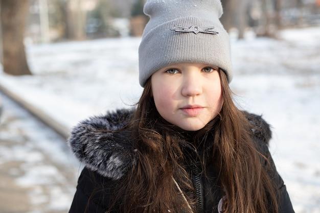 Porträt eines traurigen mädchens in einem winterpark