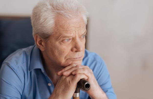 Porträt eines traurigen nachdenklichen älteren mannes, der einen spazierstock hält und sich darauf stützt, während er über seine vergangenheit nachdenkt
