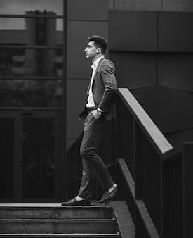 Porträt eines trendigen mannes in vollem anzug und slippern. wegschauen