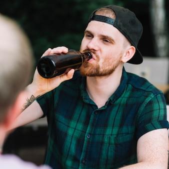 Porträt eines trinkenden bieres des gutaussehenden mannes in der flasche