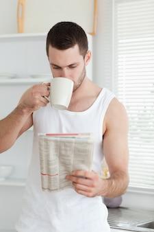 Porträt eines trinkenden tees des mannes beim lesen der nachrichten