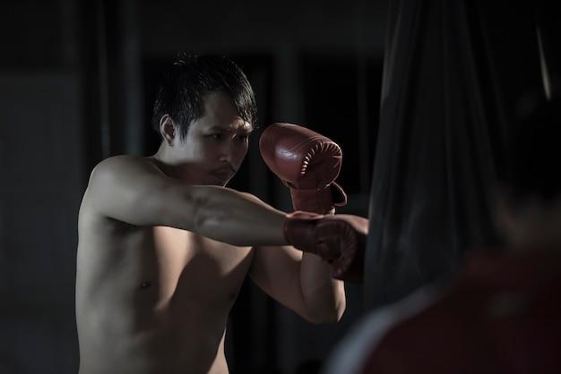 Porträt eines übenden boxens des jungen asiatischen mannes auf einem sandsack an der turnhalle.