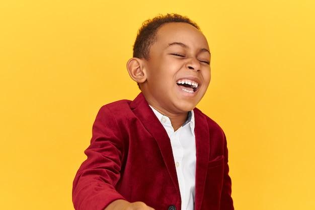 Porträt eines überglücklichen glücklichen afrikanischen kleinen jungen in der trendigen jacke, der kopf zurück wirft, während über witz laut lacht, spaß hat