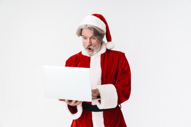 Porträt eines überraschten alten mannes mit rotem weihnachtsmann-kostüm, der laptop isoliert auf weiß hält und benutzt