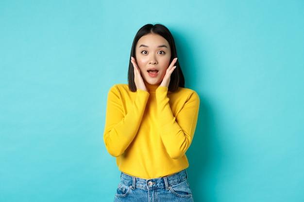 Porträt eines überraschten asiatischen mädchens, das promo auscheckt, erstaunt nach luft schnappt und wangen berührt, die kamera erstaunt anstarrt, blauer hintergrund.